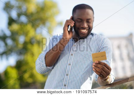 Making an order. Happy ambitious wonderful man using his credit card for buying things online and answering a phone call for confirmation