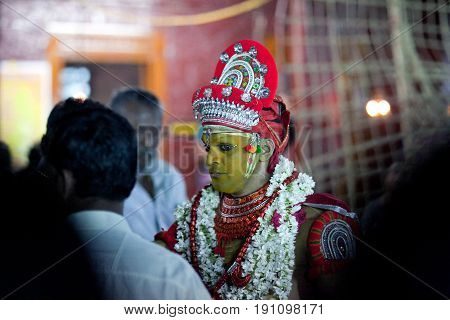 KANNUR, INDIA - JANUARY 15, 2016: Indian priest conducts Theyyam ceremony at Arathil Bhagavathi Temple in Kannur, South India. Theyyam is a ritualistic folk art form of North Malabar in Kerala.