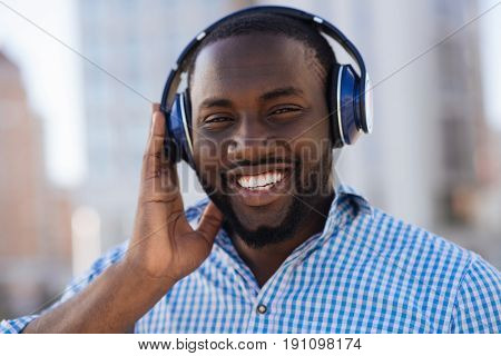 Motivating sounds. Active ambitious cheerful guy taking a stroll around the town while feeling energetic and listening to some of his favorite songs