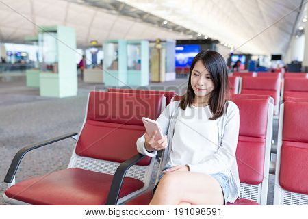 Woman sending sms on cellphone in airport