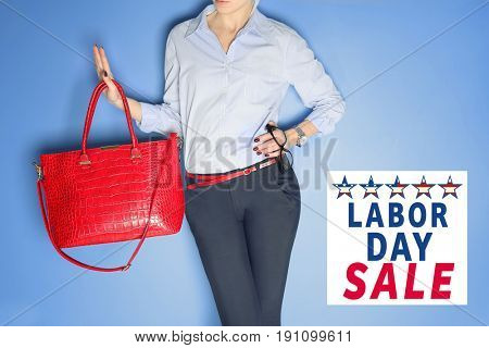 Concept of LABOUR DAY SALE. Woman with stylish bag on color background