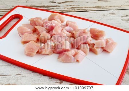 Chicken fillet cut in cubes on a white cutting board. Step by step cooking