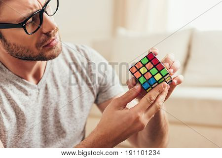 Close-up Portrait Of Serious Young Man In Eyeglasses Holding Rubik Cube