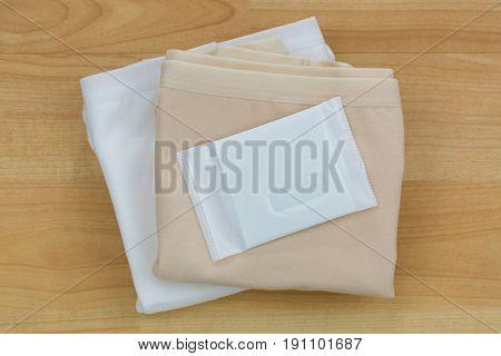 New unused Sanitary napkins (sanitary towel, sanitary pad, menstrual pad) on folded beige white underwear on wooden background