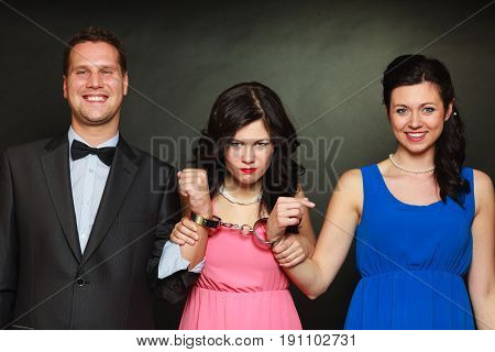 Couple cheating problems love triangle concept. Wife and husband in handcuffs jealous woman standing behind them