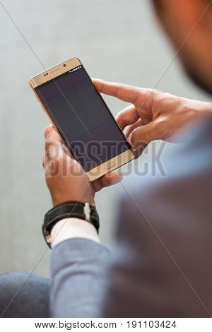 Close up of a businessman using smart phone. Focus on mobile device. Copy space.