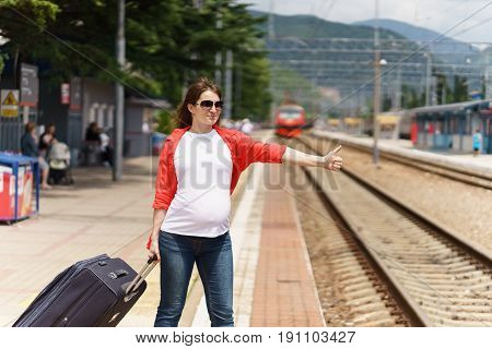 young european pregnant woman with sunglasses and heavy baggage trying to stop train on railway station for traveling at sunny day