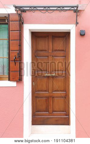 Retro wooden entrance door on house with pink facade wall