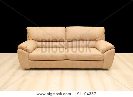 Comfortable beige leather sofa on wooden floor and black wall