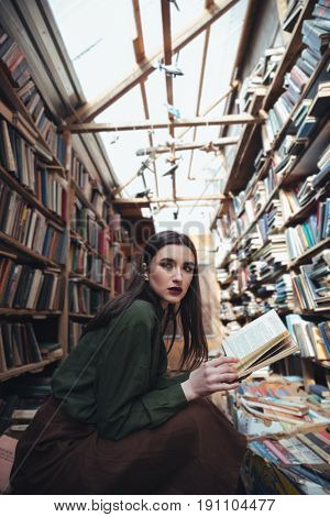 Young brunette woman with opened book looking aside while sitting among books in library