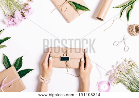 Female Hands With A Manicure Hold A Box With A Gift And Ribbon On A White Table.