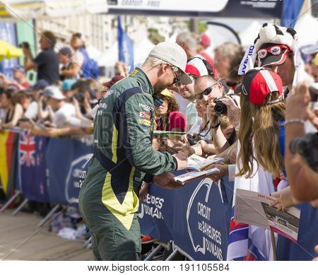 LE MANS, FRANCE - JUNE 11, 2017: Famous Danish racer Nicki Thiim gives autograph for fans Weighing, administrative and technical checks of the race cars for competition 24 hours of Le mans circuit