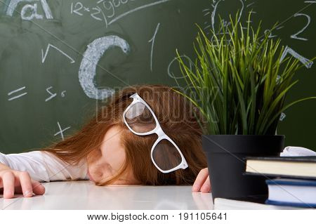 Schoolgirl tired, schoolgirl with glasses on background of board.