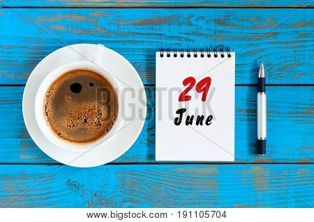 June 29th. Image of june 29 , daily calendar on blue background with morning coffee cup. Summer day, Top view.