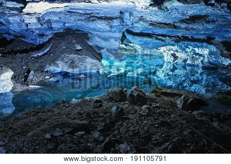 Slope of the mountain with the reflection in the water inside a fantastic cave. Kungur In Urals