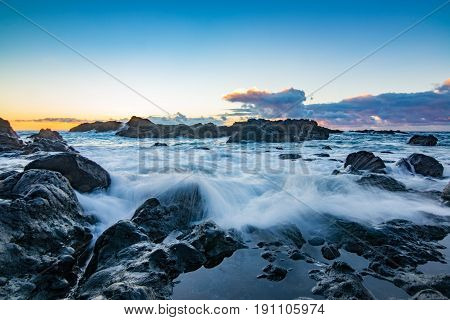 Rocky Shore Over The Ocean During Sunset.