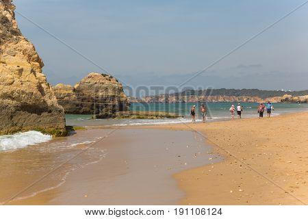 PRAIA DA ROCHA, PORTUGAL - APRIL 25, 2017: People at the beach of Praia da Rocha in Portimao. This beach is a part of tourist region of Algarve.