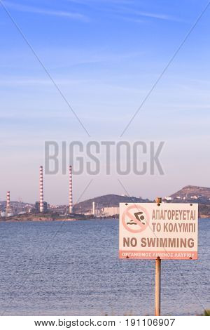 No Swimming Sign By The Beach, With Power Plant Station In The Background. Lavrio, Greece.