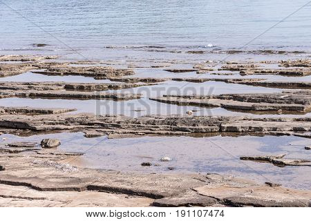 Shallow waters on rocky layered beach .