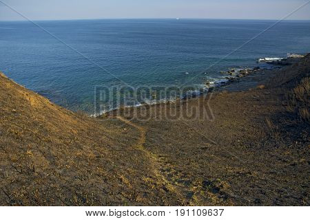 high cliff above the sea, the cliff descends into the sea, many splashing waves and stones