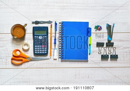 View of a wooden table with a notebook, pen, pencil, rubber, scissors, sellotape, calipers, stapler, clips, pins, calculator and a cup of coffee in a nice order