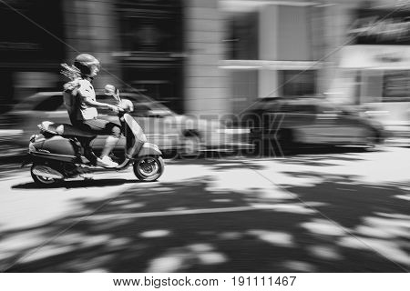 Blurred motion of a motorcyclist driving in the city.
