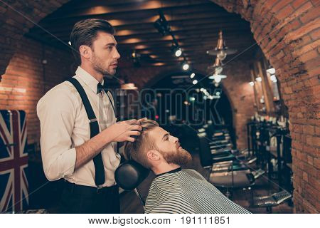 Barber Shop Classy Dressed Specialist Is Styling The Hair Of A Client. Salon Is Retro And Vintage. C