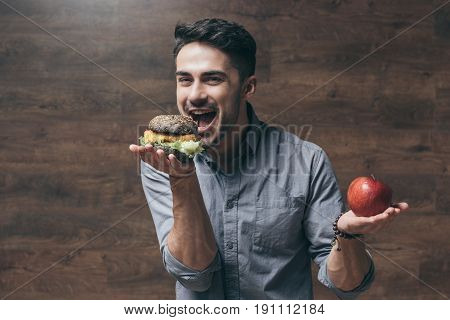 Smiling Young Man Holding Red Apple And Biting Tasty Hamburger