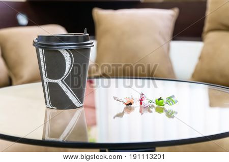 Close up coffee in black paper cup with two sweets on modern table