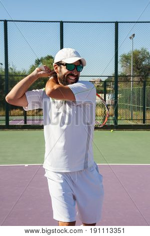 Professional tennis player with face of effort doing a tennis kick with the racket on a tennis court on a sunny day.