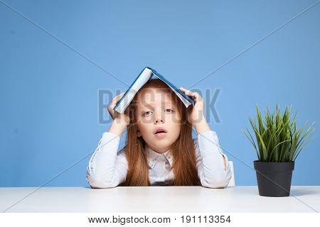 Schoolgirl holding book over head on blue background.