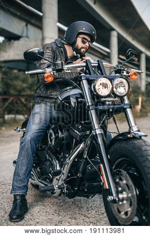 Outdoor lifestyle portrait of handsome biker man sitting on a motorcycle. Biker man wearing jeans and leather jacket sitting on motorbike.