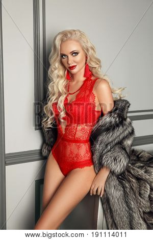 Sexy alluring blond woman in red lingerie posing in fashion fur coat by the wall in luxury modern interior. Beauty glamour style photo portrait.