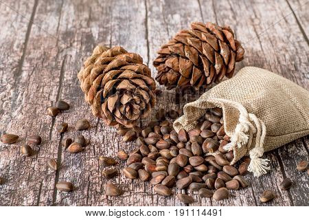Cedar cones and a small sack of nuts on a old wooden background.