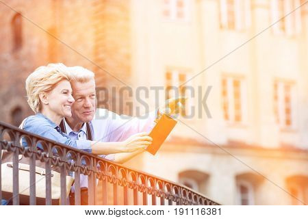 Smiling middle-aged man showing something to woman with guidebook in city