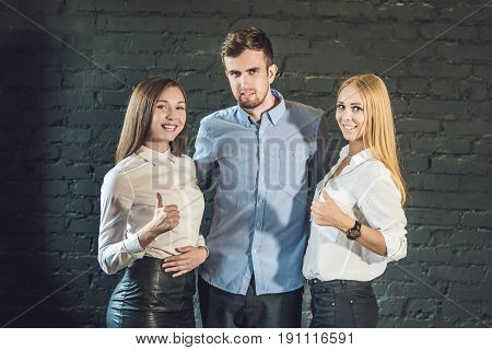 Business Team Male And Female Formed Of Young Businessmen Standing Over A Dark Background