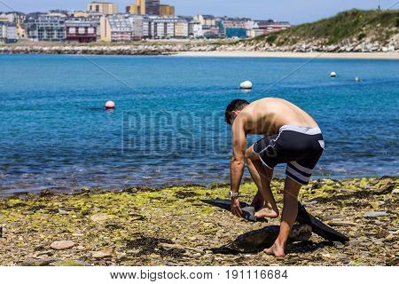 A guy getting ready to swim with fins