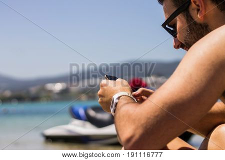 A guy using his phone while sunbathing next to his jet ski