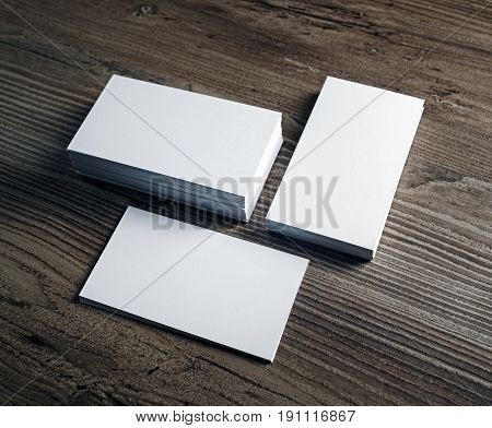 Three stacks of blank business cards stacks on wood table background. Template for your design.