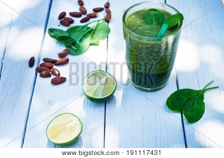 Spinach smoothie on a wooden white background. Glass of smoothie with leaves of spinach, nuts, limes. Healthy food. Breakfast. Natural light.