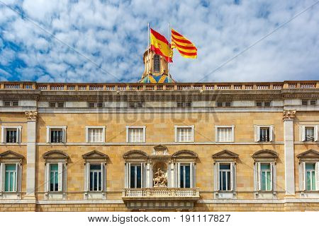 The building of the Government of Catalonia or Generalitat de Catalunya with Catalan and Spain flags on the Placa de Sant Jaume in Old Town of Barcelona, Spain