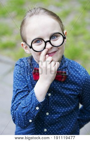 young blond boy with bow tie and big glasses is picking his nose