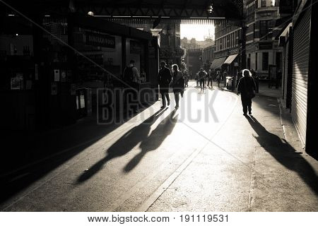 London, UK - 29 Sept 2016: End of day at Borough Market in Southwark. People make their way out of the market as it closes. Street style black and white image capturing evening low light and shadows.