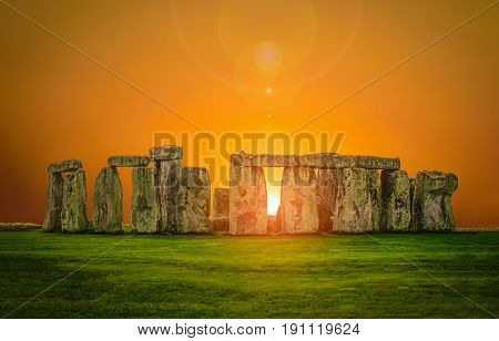 Stonehenge an ancient prehistoric stone monument at sunset with len flare in Wiltshire UK.