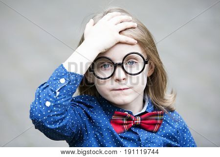 portrait of blond boy with bow tie and big glasses looking upset