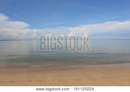 Seascape with flat sea and white clouds.