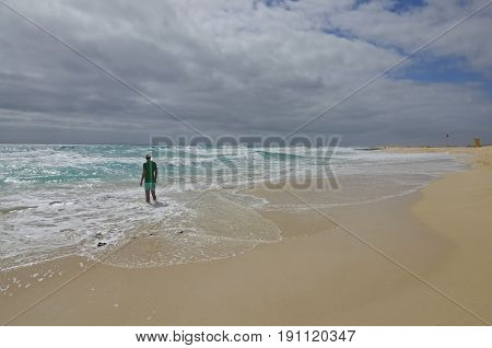 A man standing on the beach with his feet in the sea on a cloudy stormy day
