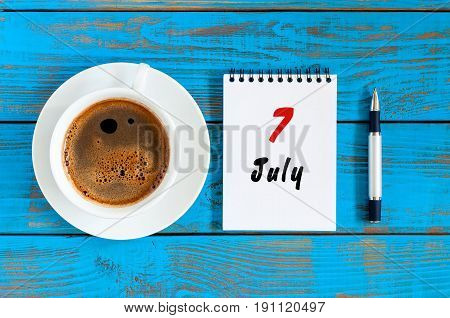July 7th. Day 7 of month, calendar on blue wooden table background with morning coffee cup. Summer concept.