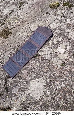 Portable solar panels lie on a rocky shore and accumulate energy.