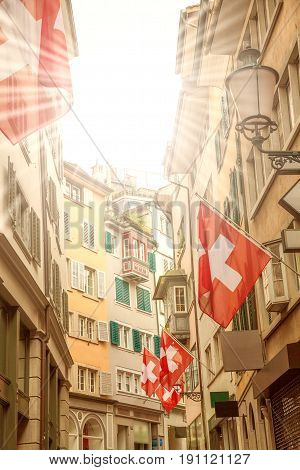 Old street with old colorful buildings with bay window balconies decorated with national flags Zurich Switzerland.
